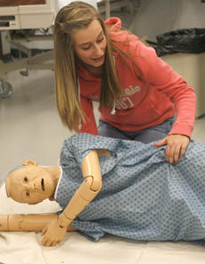 """<div class=""""source"""">Matt Birkholtz</div><div class=""""image-desc"""">Courtney Straley helps put the mannequin on its side to show the recovery position.</div><div class=""""buy-pic""""><a href=""""/photo_select/13194"""">Buy this photo</a></div>"""