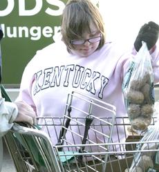 "<div class=""source"">Linda Lawrence</div><div class=""image-desc"">Kara Norris puts potatoes in carts at the mobile Free Store Food Bank on Nov. 8.</div><div class=""buy-pic""><a href=""http://web2.lcni5.com/cgi-bin/c2newbuyphoto.cgi?pub=195&orig=IMG_6472.jpg"" target=""_new"">Buy this photo</a></div>"