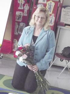 """<div class=""""source"""">Paige Taylor</div><div class=""""image-desc"""">judy Olliges displays her flowers that she received from her students.</div><div class=""""buy-pic""""><a href=""""/photo_select/10857"""">Buy this photo</a></div>"""