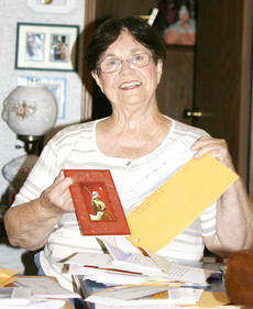 "<div class=""source"">Linda Lawrence</div><div class=""image-desc"">Rosalie Tunks prepares to mail gift certificates and Christmas cards for service members who are stationed  in the states.</div><div class=""buy-pic""></div>"