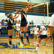 """<div class=""""source""""></div><div class=""""image-desc"""">Macall Knight, a junior at Grant County High School, prepares to hit the ball as Ashley Marksberry, a sophomore, and Rachel Montgomery, a freshman, prepare to block the ball during a crosstown match up of the Lady Braves and Lady Demons on Aug. 30. The Lady Demons won after being down early in the game. Photo by Haleigh Jacobs</div><div class=""""buy-pic""""><a href=""""/photo_select/15665"""">Buy this photo</a></div>"""