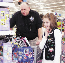 """<div class=""""source"""">Bryan Marshall, staff writer</div><div class=""""image-desc"""">Terry Peoples, a sergeant at the Grant County Detention Center helped Chelsey shop during the annual Shop With A Cop program held Dec. 12. </div><div class=""""buy-pic""""><a href=""""http://web2.lcni5.com/cgi-bin/c2newbuyphoto.cgi?pub=195&orig=girl.jpg"""" target=""""_new"""">Buy this photo</a></div>"""