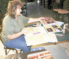 """<div class=""""source"""">Jamie Baker-Nantz</div><div class=""""image-desc"""">JoAnn Hamberg, a member of the Lunch and Learn Homemakers Club, enjoys documenting life's journey in scrapbooks. Photo by Jamie Baker-Nantz</div><div class=""""buy-pic""""><a href=""""/photo_select/11616"""">Buy this photo</a></div>"""