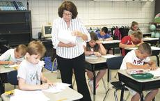 """<div class=""""source"""">Paige Taylor</div><div class=""""image-desc"""">Linda Harrison hands out open response papers to her students.</div><div class=""""buy-pic""""><a href=""""/photo_select/10856"""">Buy this photo</a></div>"""