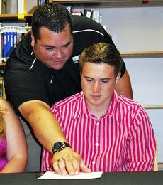 """<div class=""""source"""">Camille McClanahan</div><div class=""""image-desc"""">Brian Chapman is shown where to sign his name to become a Union College soccer player. </div><div class=""""buy-pic""""><a href=""""/photo_select/14176"""">Buy this photo</a></div>"""