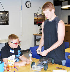 "<div class=""source""></div><div class=""image-desc"">Cole Barnes shows London Fry how to work on a robot.  </div><div class=""buy-pic""><a href=""/photo_select/18171"">Buy this photo</a></div>"