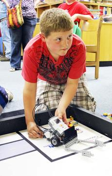 """<div class=""""source""""></div><div class=""""image-desc"""">Wyatt Auel explains his robot to his friends and family. Each student in the Student Technology Leadership Program and Robotics class was assigned to design and build a program. </div><div class=""""buy-pic""""><a href=""""/photo_select/17913"""">Buy this photo</a></div>"""