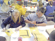 """<div class=""""source""""></div><div class=""""image-desc"""">Jacy Adams and Derek Cummins glue fliers requesting non-perishable food donations onto paper bags that were distributed throughout the county.</div><div class=""""buy-pic""""><a href=""""/photo_select/12739"""">Buy this photo</a></div>"""