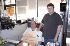 "<div class=""source"">Bryan Marshall</div><div class=""image-desc"">Jackie Miller, left, and his son, Jackie Jr., sit behind the counter at Jack's General Store.