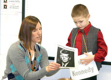 """<div class=""""source""""></div><div class=""""image-desc"""">WES teacher Emily Barker assists Charley Fryman during his speech about President John F. Kennedy.</div><div class=""""buy-pic""""><a href=""""/photo_select/20224"""">Buy this photo</a></div>"""
