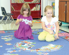 """<div class=""""source""""></div><div class=""""image-desc"""">Emily Richardson, left, and Caylee Ann Rarrieck, right, work on a puzzle together during CMZ Kindercamp. The program helps get incoming kindergartners ready for school. Photos by Bryan Marshall</div><div class=""""buy-pic""""><a href=""""/photo_select/21490"""">Buy this photo</a></div>"""