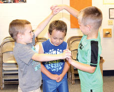 """<div class=""""source""""></div><div class=""""image-desc"""">Gage McCann and a fellow incoming kindergartner student at CMZ trap John Foltz in their bridge during a music exercise utilizing """"London Bridges Falling Down.""""</div><div class=""""buy-pic""""><a href=""""/photo_select/21492"""">Buy this photo</a></div>"""