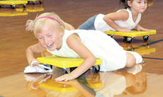 """<div class=""""source""""></div><div class=""""image-desc"""">Haleigh Dunn laughs while trying to scoot herself on the gym floor.</div><div class=""""buy-pic""""><a href=""""/photo_select/21493"""">Buy this photo</a></div>"""