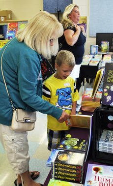 "<div class=""source""></div><div class=""image-desc"">Kamden Kerinuk tells his grandmother about a book in the Sherman Elementary book fair. </div><div class=""buy-pic""><a href=""/photo_select/19172"">Buy this photo</a></div>"