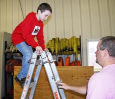 "<div class=""source""></div><div class=""image-desc"">Jordan Rudd climbs over a ladder in the obstacle course at the Dry Ridge Firehouse. </div><div class=""buy-pic""><a href=""/photo_select/19328"">Buy this photo</a></div>"