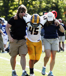 """<div class=""""source""""></div><div class=""""image-desc""""> Triston Wallace needs help off the field after an injury.  </div><div class=""""buy-pic""""><a href=""""/photo_select/18950"""">Buy this photo</a></div>"""
