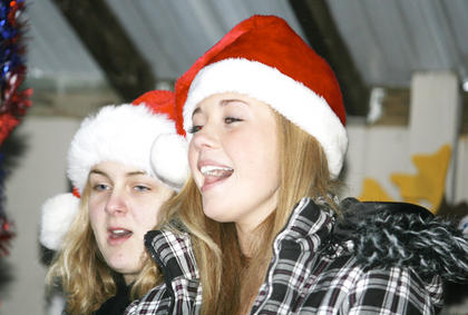 Kayla Ousley, left, and Samantha Anderson, right, of the Williamstown High School chorus, sing during Santa's Wonderland.