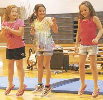 Alexis House, Taleah Dalton, and Bethany Griffin jump for joy at the talent show during their cheerleading performance.