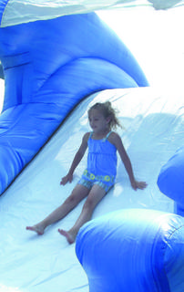 Alyssa Harper slides down the water slide at the libary's summer reading kickoff.