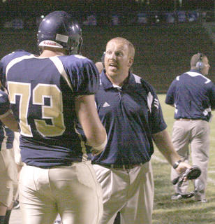 Braves football coach David Arvin yells to senior JT Allhouse after a play on the field against Owen County Aug. 27.