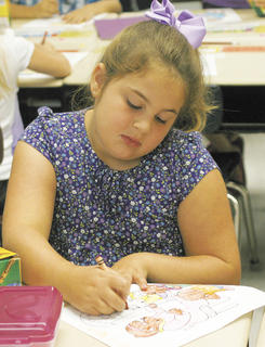 Audrey Adams works on coloring the Berenstein Bears page on the first day of school.