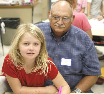 Avery Daugherty takes a break from her drawing to have a picture with her grandfather Ken Shaw.