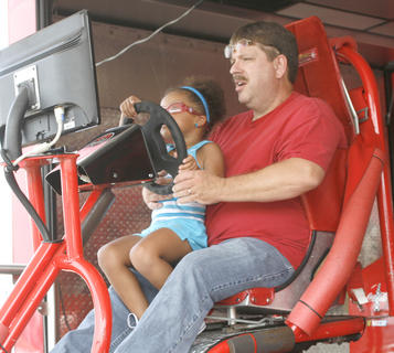 Alyssa Carr and her grandpa Randy Ratcliffe enjoy the racing simulator at Wal-Mart in Dry Ridge
