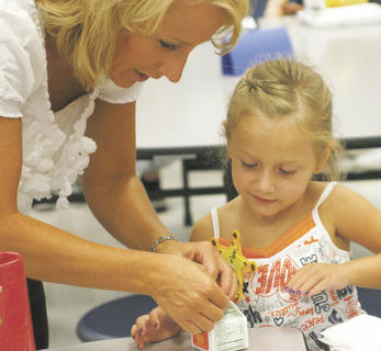 Brelynn White watches as her mother Becca shows her how to open her orange juice during Boo-Hoo Breakfast at MCE.