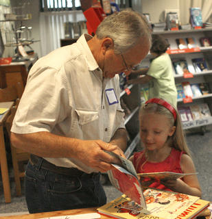 Kendall Forman and her grandfather, Barry Forman, choose a book at the book fair.