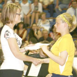 Taylor Souder gets an award from Mrs. Pope in her softball uniform. Souder came in at the last minute from a GCMS softball game.