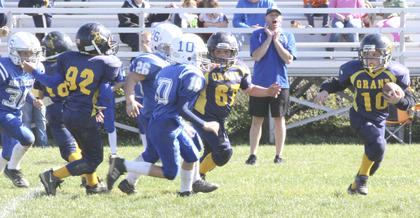 Blue Mighty Pro Bryant Henson attempts a touchdown, while Isaiah Magee (67) and Austin Darghty (92) try to hold off Walton-Verona.