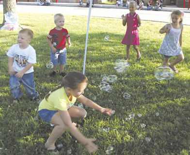 Kids play with bubbles while Cheryl Clemons from the Grant County Library reads them a story.