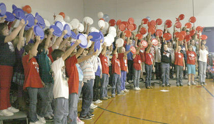 CMZ Elementary students create a wave of red, white and blue during a Veterans Day cemetery.
