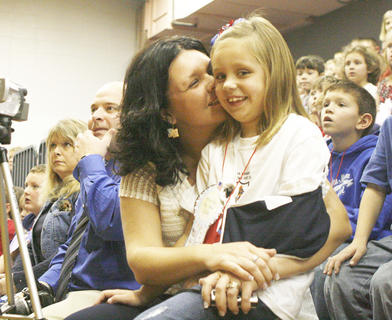 Crittenden-Mt. Zion Elementary Heather Clay gives her daughter Kinsey a hug during a video presentation that included her husband during a Veterans Day assembly. 