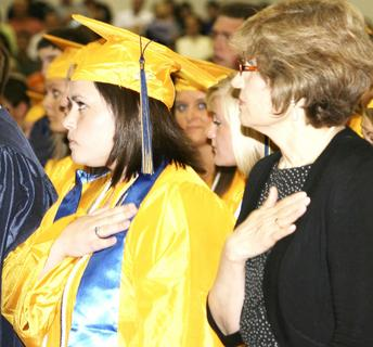 Rebekah Carey and retiring teacher Pat Conrad stand in respect during the playing of the National Anthem.