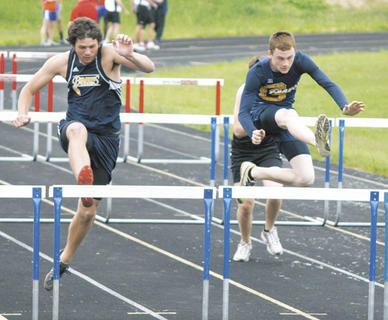 Braves senior Cory Kearns and eighth grader Brent Young compete in the 100 meter hurdles.