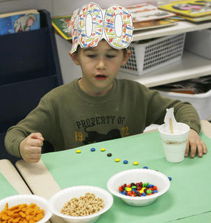 Payton Mahoney, counts Skittles, Cheerios and Cheddar Whales, 20 at a time, as part of the 100th day of school at Mason-Corinth Elementary.