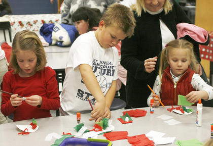 From left to right, Haleigh Hillman, Cason Jones and Kirsten Gillispie make some crafts at the MCE Holiday Cafe.