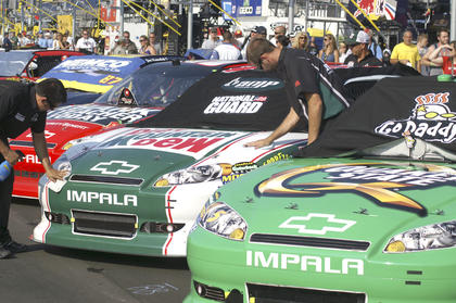 Crew for Dale Earnhardt Jr. work on cleaning his car before the race.