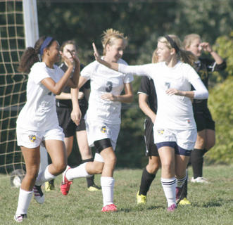 Lady Braves sophomore Dana Liggett claps with teammate Alexis Willen after scoring her first goal of the season.
