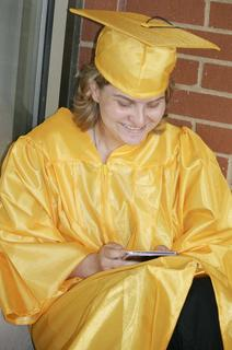 "Elizabeth ""E.J."" Faulkner spends time texting before graduation ceremonies begin."
