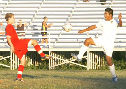 Braves soccer player Eddie Maya kicks his leg high for the ball against Scott County.