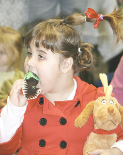 Gracey Coghill, 4, of Dry Ridge enjoys a cupcake at the Grinch Party at the Grant County Public Library.