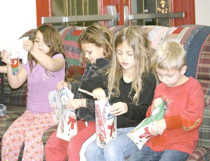 Children who live at Meadow View enjoyed a family Christmas party in the Community Center sponsored by Dry Ridge Baptist Church Sunday Night Activities for Children. Haley Zabela, Sarah Frazure, Alyssa Harper and her brother Isaiah open gifts.