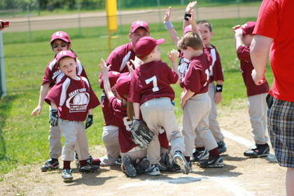 The Thoroughbreds gather around coach Todd Moore after playing their first t-ball game of the season.