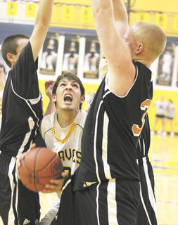Braves senior guard Andrew Hurley tries to squeeze through David Jump and Colton Simpson for the shot.