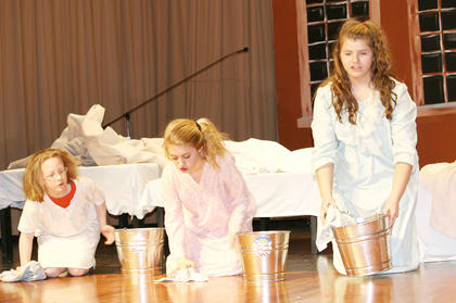 CJ Verbeck, Sabryn Wooten and Annelise Kinsey the scrub floors of the orphanage.