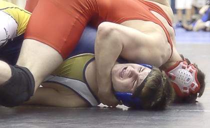 Isaac Magee grimaces as he gets pinned during the match.