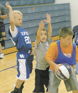 Jackson Smallwood, right, 7, of Dry Ridge looks for an opening as Jake DIetz, 7, of Sherman and Brant Smithers, 7, guard the lane.