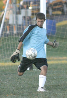 Braves freshman goalkeeper Jordan Kearns kicks the ball back into play after saving a goal against Scott County.